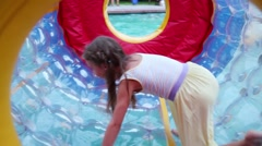 Stock Video Footage of Happy girl in dress runs in big inflatable cylinder on water