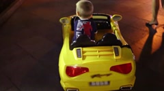 Back of little boy riding on yellow electric car at night street Stock Footage