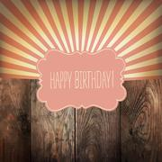Happy Birthday greeting card with sunrays and vintage label. On wooden backgr - stock illustration
