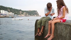 Boy and girl sits with fishing rod on concrete pier near sea Stock Footage