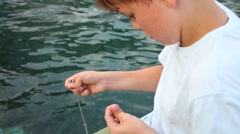 Boy with fishing rod prepares for fishing near water of sea Stock Footage