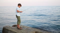 Handsome boy fishes in sea on concrete pier at summer Stock Footage