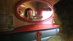 Woman in business-class compartment of train looks in mirror Stock Footage