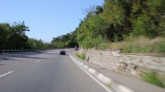 Cars move on road turn among trees at summer sunny day Stock Footage