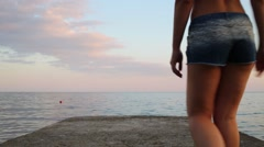 Back of woman in shorts going on concrete pier near sea Stock Footage