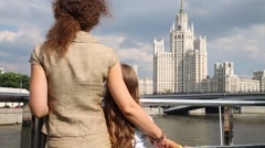 Back of mother and girl looking at building from river ship Stock Footage