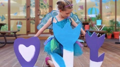 Pretty girl in fairy costume in cafe plays with big toy flowers Stock Footage