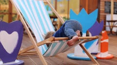 Little boy tries to get out of sun lounger in cafe with veranda Stock Footage