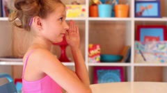 Little girl sits at table and raises hand in play room with shelves Stock Footage