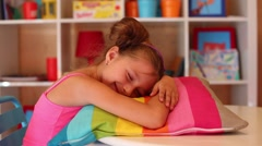 Little girl pretends to be asleep on pillow on table at game room Stock Footage