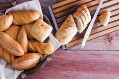 Sliced baguette and rolls on a buffet table - stock photo