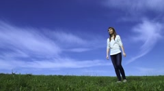 Young happy woman is jumping in front of the camera. Blue sky and green grass  Stock Footage