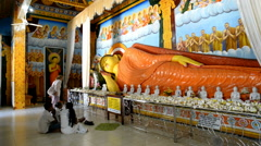 Pilgrims praying at the statue of Buddha in Abayagiri Dagoba in Anuradhapura, Sr Stock Footage