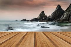Rugged long exposure landscape seascape of rocky coastline with wooden planks Stock Photos