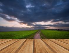 Moody sky over countryside landscape of path leading into distance with woode Stock Photos