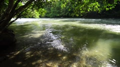 Clean fresh water river with visible rocky riverbed at deep jungle. Stock Footage