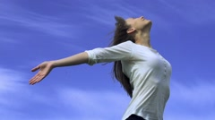 Young woman is standing with her arms open to the wind, enjoying the breeze  Stock Footage