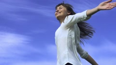 Attractive young woman dancing outdoors on a blue sky background. Slow motion, - stock footage