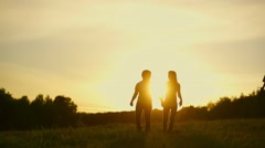 Romantic young couple silhouette are holding hands and running forward  Stock Footage