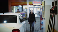 Stock Video Footage of Woman refueling car at gas station pump at night