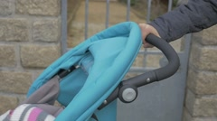 Mother pushing pram  outdoors  slow motion 1080p FullHD footage - Outdoor walk Stock Footage