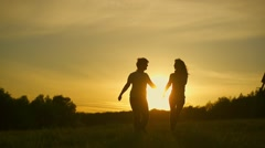 Romantic young couple silhouette are holding hands and running forward  - stock footage