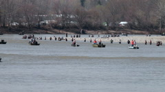 Crowded fishing spot, fishermen wading and in boats lining the river Stock Footage