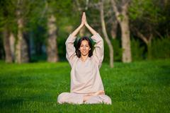 Practicing yoga in the morning, with trees  background - stock photo