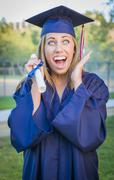 Expressive Young Woman Holding Diploma in Cap and Gown Outdoors Stock Photos