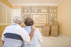 Hugging Senior Couple In Empty Room with Shelf Design Drawing on Wall. Stock Photos