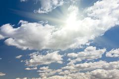 Beautiful Deep Blue Sky and Puffy Clouds With Sun Rays. Stock Photos