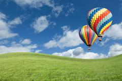 Two Hot Air Balloons Up In The Beautiful Blue Sky With Grass Field Below. - stock photo