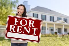 Excited Mixed Race Female Holding For Rent Sign In Front of Beautiful House. Stock Illustration