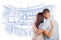 Stock Photo of Curious Young Military Couple Looking Over Custom Kitchen Design Drawing.