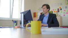 Slow motion of a nice business man in office satisfied in front of screen Stock Footage