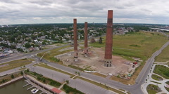 Implosion of two smoke stacks, demolition seen from the air Stock Footage