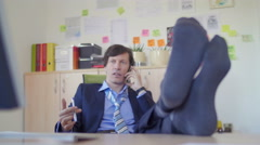 Business man talking over phone with feet on the desk Stock Footage