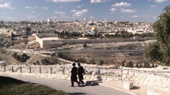 Old city of Jerusalem with two Rabbis walking in front Stock Footage