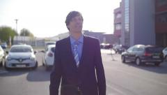 Slow motion of a young businessman walking happy in a parking Stock Footage