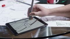 Stock Video Footage of 4K Hands using computer tablet with creative automotive design drawings