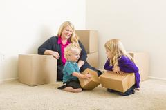 Happy Young Family in Empty Room With Moving Boxes. - stock photo
