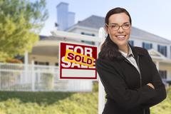 Attractive Mixed Race Woman in Front of House and Sold Real Estate Sign. - stock photo