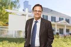 Male Real Estate Agent in Front of Blank Home For Sale Sign and House. Stock Photos