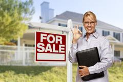 Female Real Estate Agent in Front of Home For Sale Sign and House. Stock Illustration