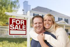 Affectionate Happy Couple in Front of New House and For Sale Real Estate Sign - stock photo