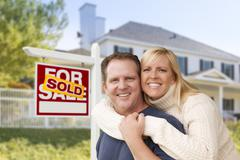Couple in Front of New House and Sold Sign Stock Photos