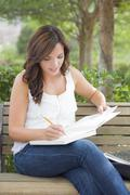 Attractive Young Adult Female Student on Bench Outdoors with Books and Pencil - stock photo