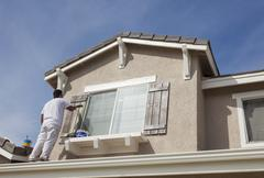 Busy House Painter Painting the Trim And Shutters of A Home. Stock Photos