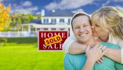 Happy Couple Hug In Front of Sold Real Estate Sign and Beautiful New House Stock Illustration