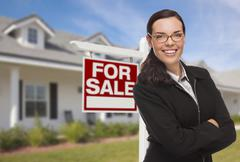 Attractive Mixed Race Woman in Front of House and For Sale Real Estate Sign. - stock photo